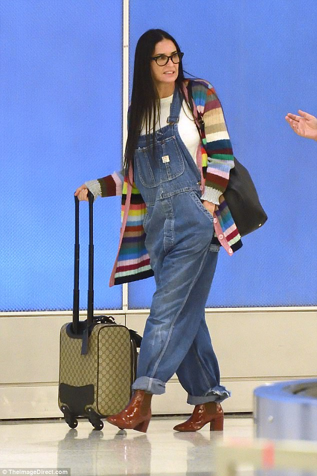 Jet-setter: The actress showed off her smooth complexion as she wore a youthful ensemble of a multicolored cardigan and denim dungarees for her flight
