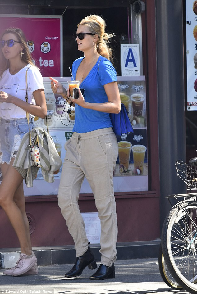 Cool customer:Tori rocked a low-cut blue blouse that flashed a hint of cleavage, a pair of khaki sweats, and black leather ankle boots with a chunky heel