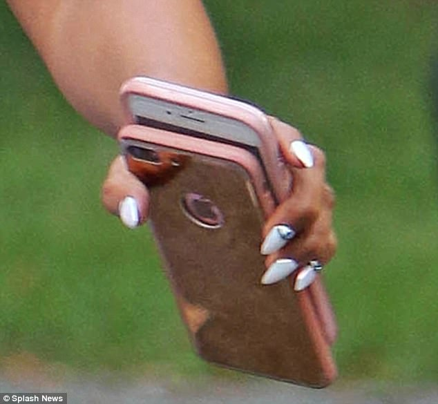 Well connected! The star carried a pair of smartphones as she made her way into the building