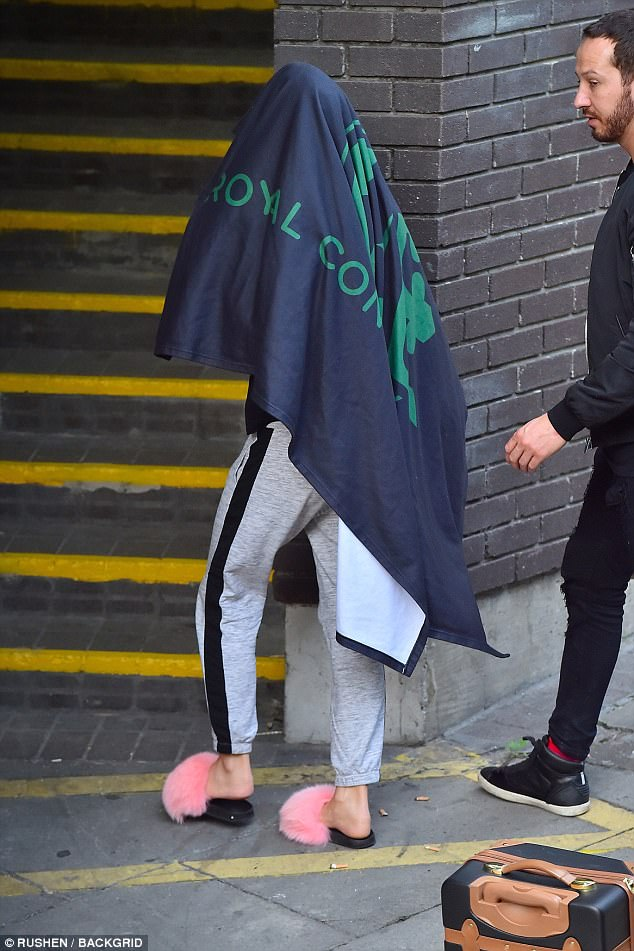 Low profile: Amid the drama, Katie was seen arriving at Loose Women with a towel over her head on Tuesday morning