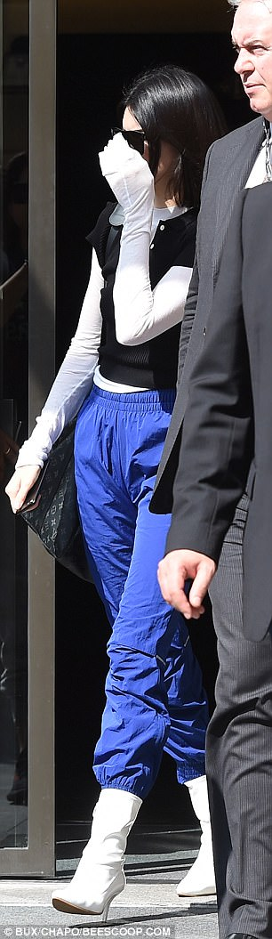 Low profile: Kendall, 21, attempted to keep a low profile as she walked briskly through the airport, holding her hand over her face before pulling her jacket over her head