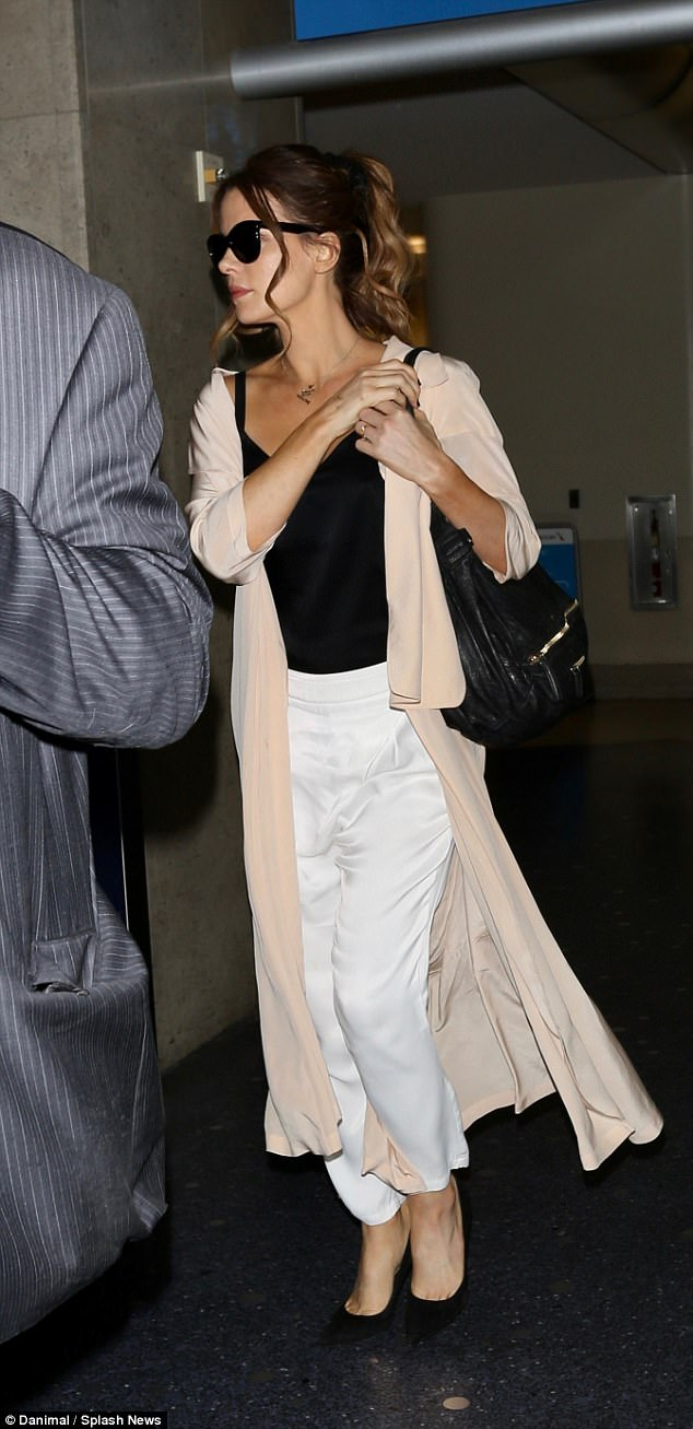 Cross-country trip: The British beauty, 44, was stylish in tailored white slacks and a long pale pink duster as she headed home after flying in from New York