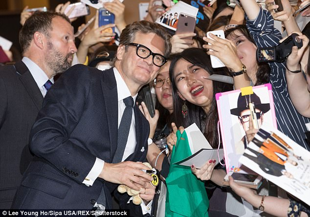 Man of the hour: The actor beamed as he posed with his fans