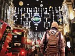 Yets another threat: The latest ISIS poster shows a jihadi draped in a bullet belt walking down Oxford Street underneath this year's Christmas lights