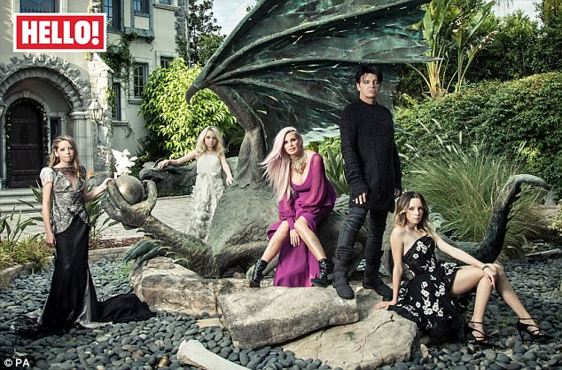 Home sweet home:Gary Numan (wearing black, pictured with his wife Gemma in pink and daughters Raven, Persia and Echo) told Hello! magazine on Monday that he has a 'very normal' family life despite his somewhat lavish taste in property