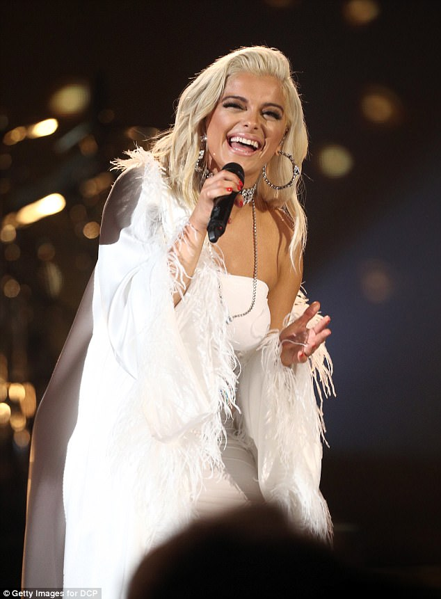 Belting it out: The musician offset her bright white outfit with a glowing tan