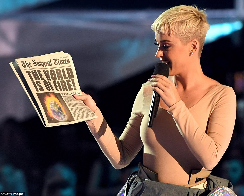 On fire: Katy held up a fake newspaper with a headline about the world being on fire