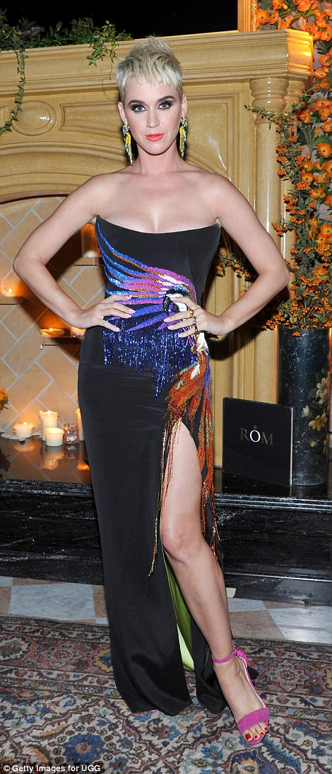 Glamourous: The pop princess stole the show in a cleavage-enhancing strapless gown with a dangerously high side-split