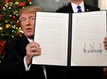 U.S. President Donald Trump holds up the proclamation Wednesday that announces the United States recognizing Jerusalem as the capital of Israel and moving its embassy there