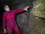 Cave explorer Daniel Caron points to a wall of a cave under a park in Montreal