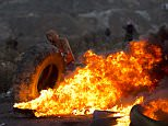 Palestinian protesters burn tyres during clashes with Israeli troops following protests on the streets of Israel
