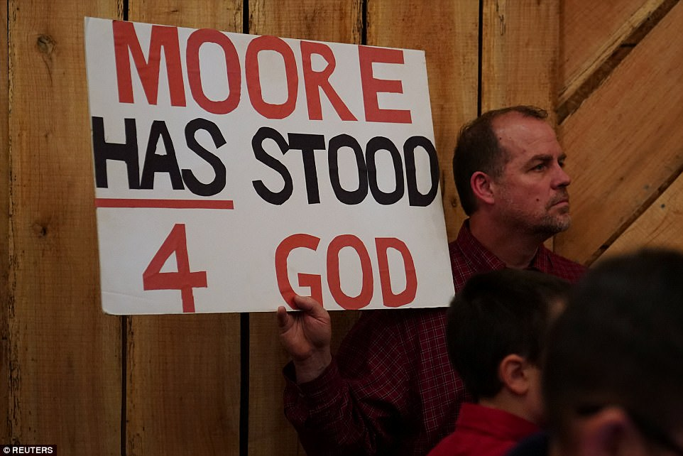 Moore called out the Washington Post specifically for producing a 'terrible, disgusting article' – which was the first story where the candidate's accusers went on the record. Pictured: A Moore supporter with a sign declaring the candidate's godliness