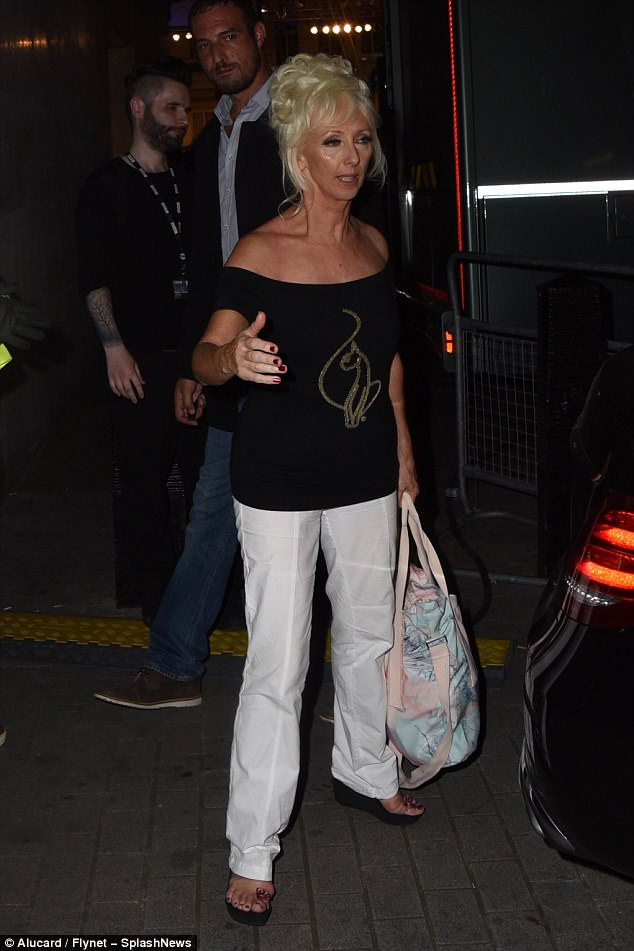 Casual glamour:She courted attention when she made her exit as she teased a glimpse of her cleavage in the scooped neckline of her black logo cat top