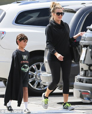 Blacked out: The ex-wife of Lamar Odom kept her honey colored locks in a bun while accessorizing with black aviators and gold hoop earrings