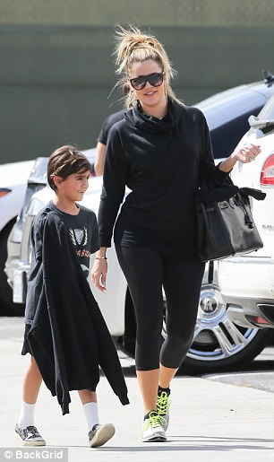 Playtime: Younger sister Khloe also wore an all black ensemble with a hoodie, workout pants and running shoes that featured neon shoelaces