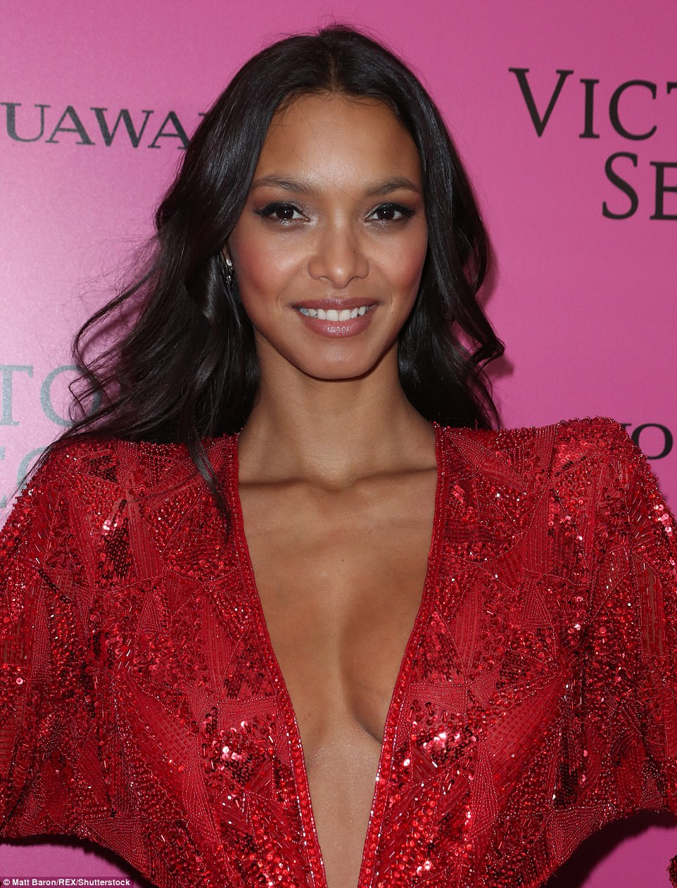 Plunging: Lais flashed her cleavage in the sparkling scarlet beaded dress as she shot the camera a winning smile