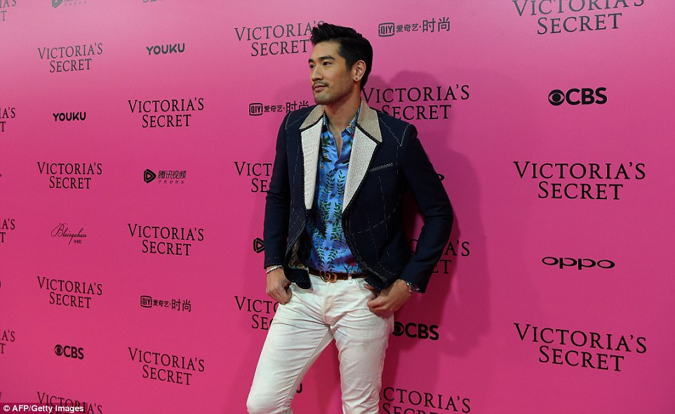 Suave: Godfrey rocked a floral shirt, white jeans and a denim jacket as he posed for snappers at the party