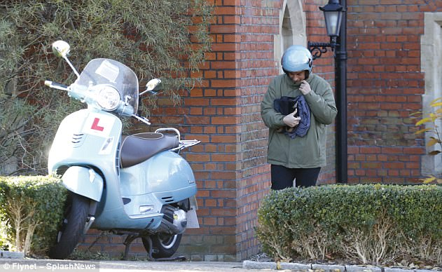 Off we go: Arg looked as if he was feeling the biting cold as he walked to his moped
