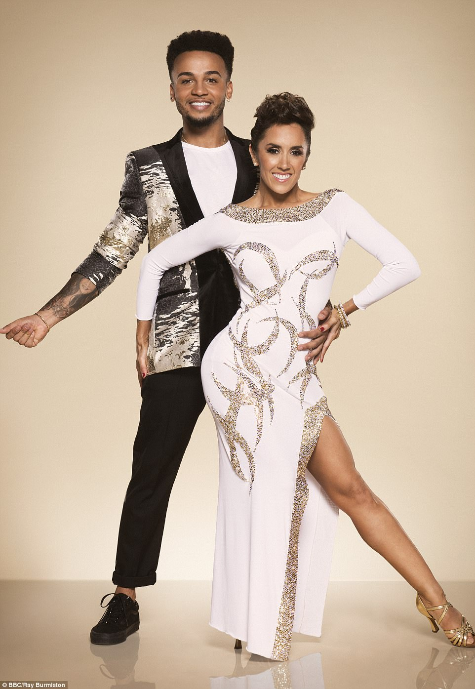 Cool kid:Boyband star Aston Merrygold added a trendy touch to the shoot in a striking metallic blazer, as he cut a cool figure clicking for the camera beside his leggy gown-clad partner Janette Manrara