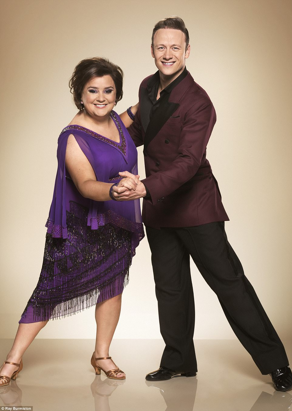 Stunning: Comedian Susan Calman looked worlds away from her usual suited and booted self as she posed gleefully beside her partner Kevin Clifton, in a stunning purple frock with soft chiffon sleeves