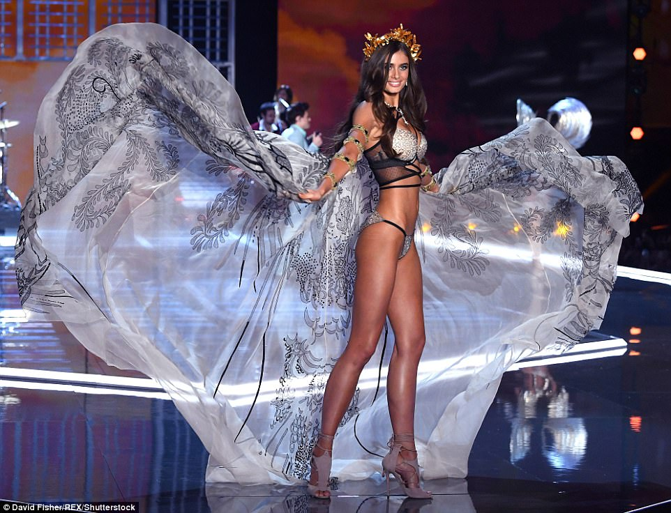 Working it: Taylor Hill used her wings to create dramatic shapes on the runway as she sashayed down