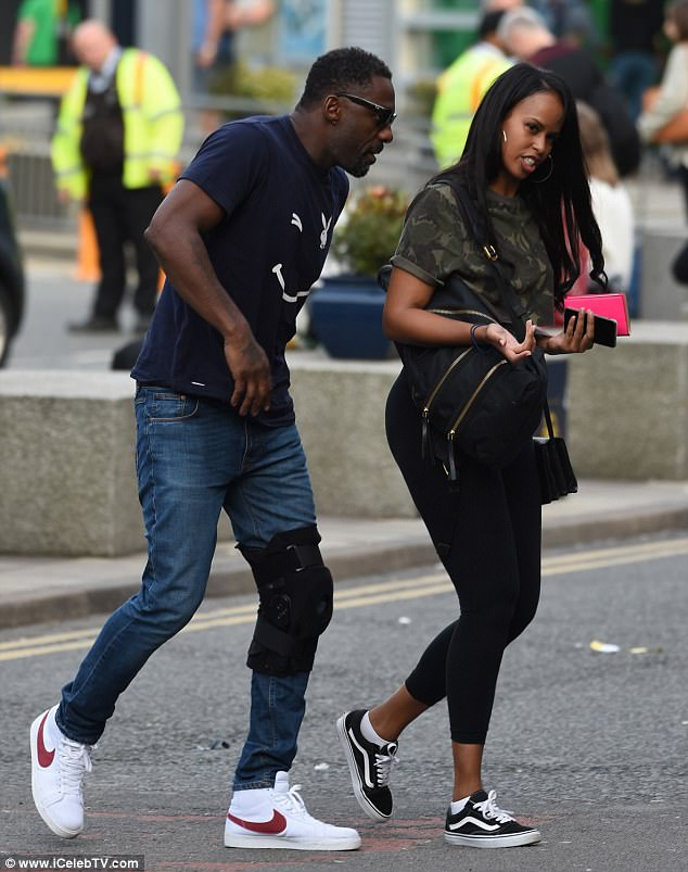 Hobbling along: Idris Elba, 44, sported a leg brace as he walked alongside a mystery woman at Manchester Airport, while wearing his Playboy T-shirt