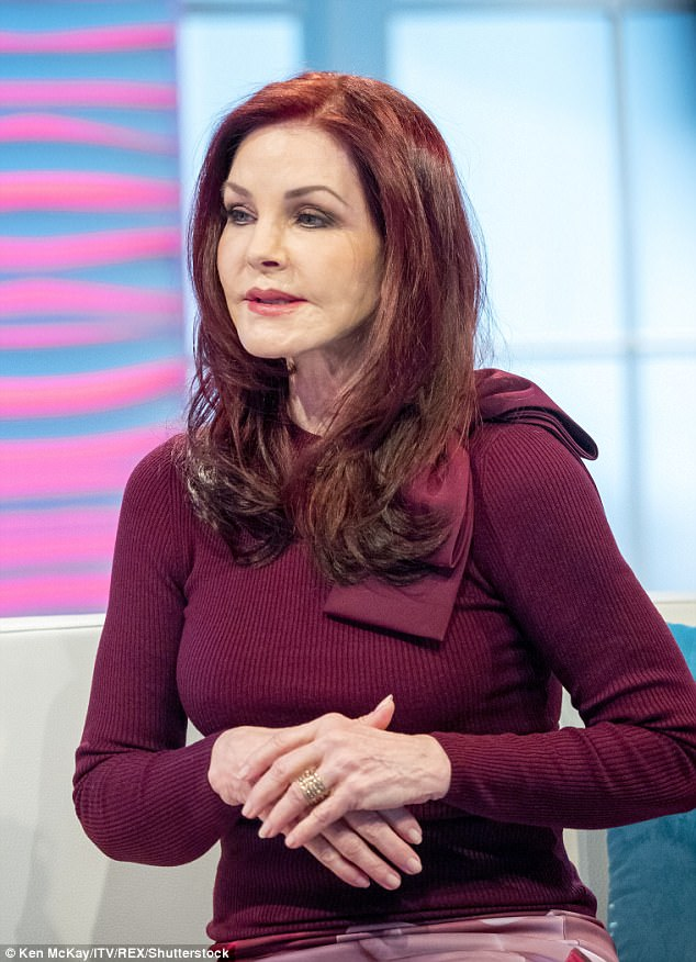 Wrapped up: Priscilla donned a burgundy coloured rib top for the occasion which featured bow detail on the shoulder