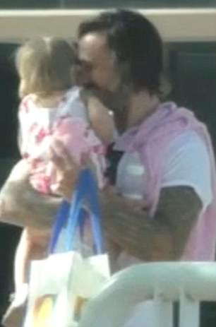 Happy dad: Corey left with his one-year-old in arm and a huge grin on his face