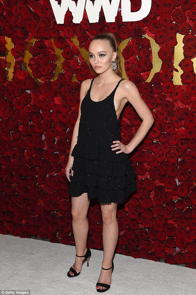 Co-ordinated: The Yoga Hosers actress painted her toenails a bright crimson red, matching the ornate flower wall backdrop