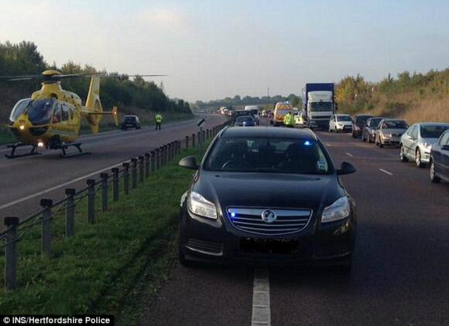 Road closure: An air ambulance lands near the spot where the crash happened on the A10 close to Ware, Hertfordshire