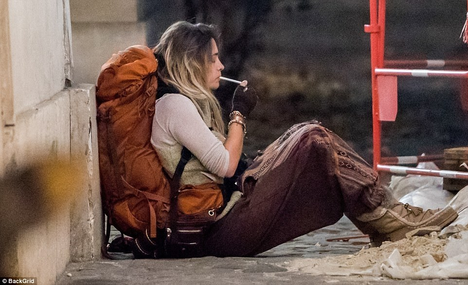 Relax: Paris closed her eyes as she put her feet up in a pile of rubble on the pavement in the capital