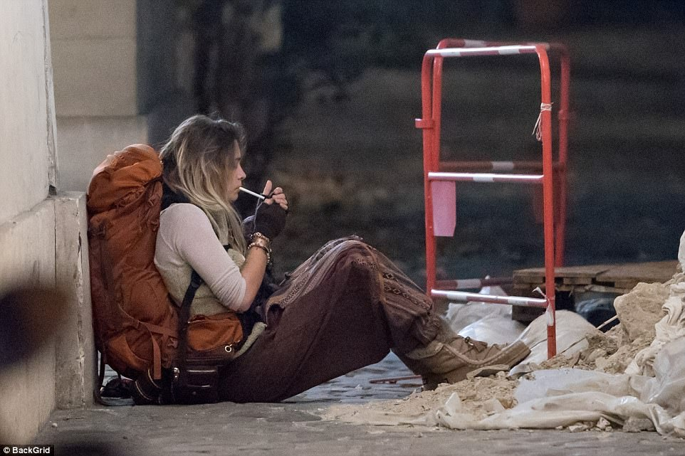 Smoke break:The make-up free star rocked a bohemian look for her backpacking trip, clad in a purple patterned pair of harem trousers paired with a cream top and an ivory gilet as she smoked on the pavement