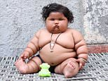 Among the spectacular individuals pictured this year was Chahat Kumar, who can be seen above playing with a toy at her house  in Punjab, India, back in March. The enormous baby -weighing in at a whopping 38lbs - has baffled doctors. The eight-month-old tot was born an ordinary weight but started ballooning in size at the age of four months. Now the bouncing bundle weighs 2.7 stones - about the same as an average four-year-old