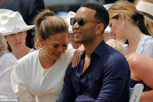 Giggle-fest: Chrissy enjoyed a laugh with her man during the tennis match