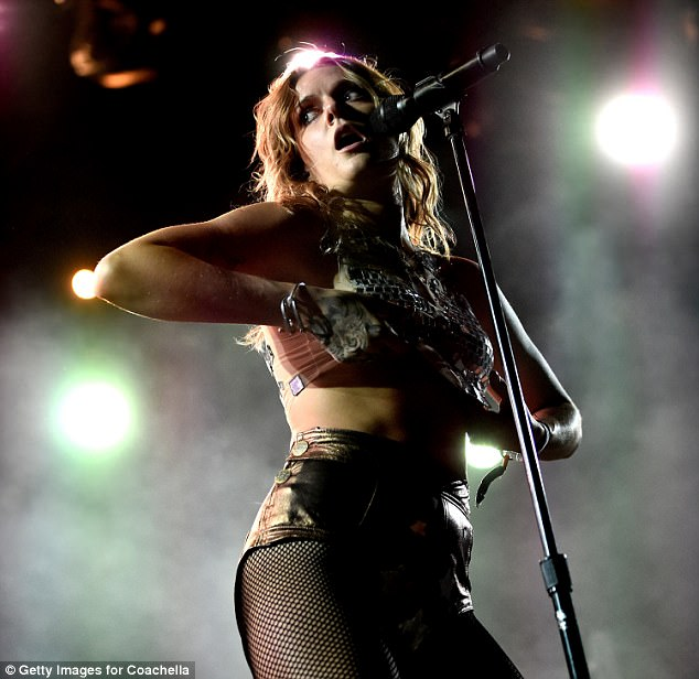 Flash: Tove lifted up her silver embellished crop top, which she paired with silver lame hotpants and fishnet tights