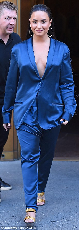 Stepping out in style: The former Disney darling sizzled in the daring navy suit jacket, which was paired with matching pants