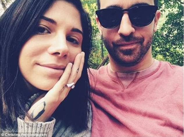 Happile ever after: The singer, 31, shared a black and white photo of herself as Paul clutched her rounded belly to announce their marriage