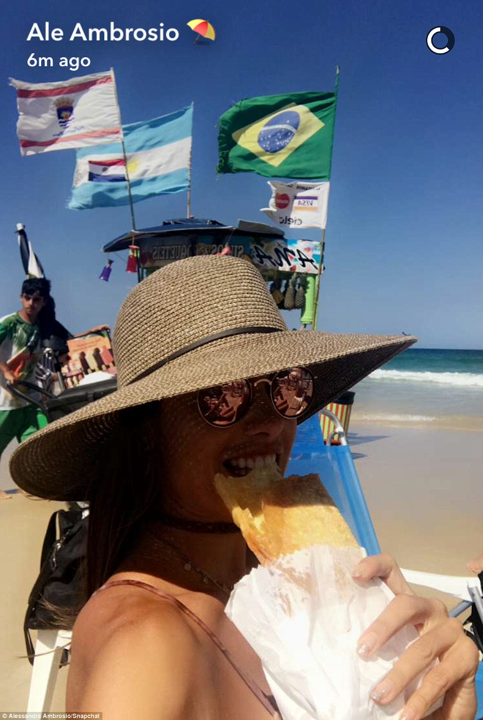 Yum: Alessandra shared this selfie while snacking on the beach