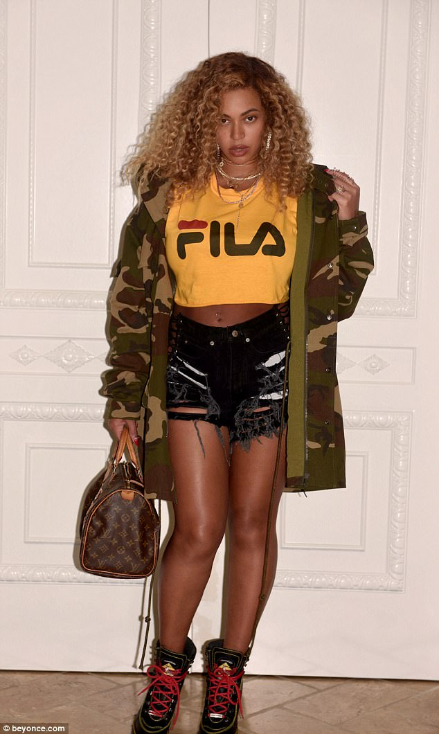Strike a pose:Beyonce chose a loose fitting yellow Fila top that had long sleeves with a Mistress Rocks Jump Up Camouflage oversized jacket