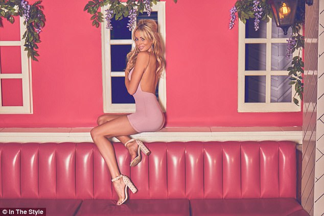 Cheeky!Feeling playful for her next shot, the blonde beauty wore an eye-wateringly small pink mini dress with a backless detail while teasing her hair into a beehive