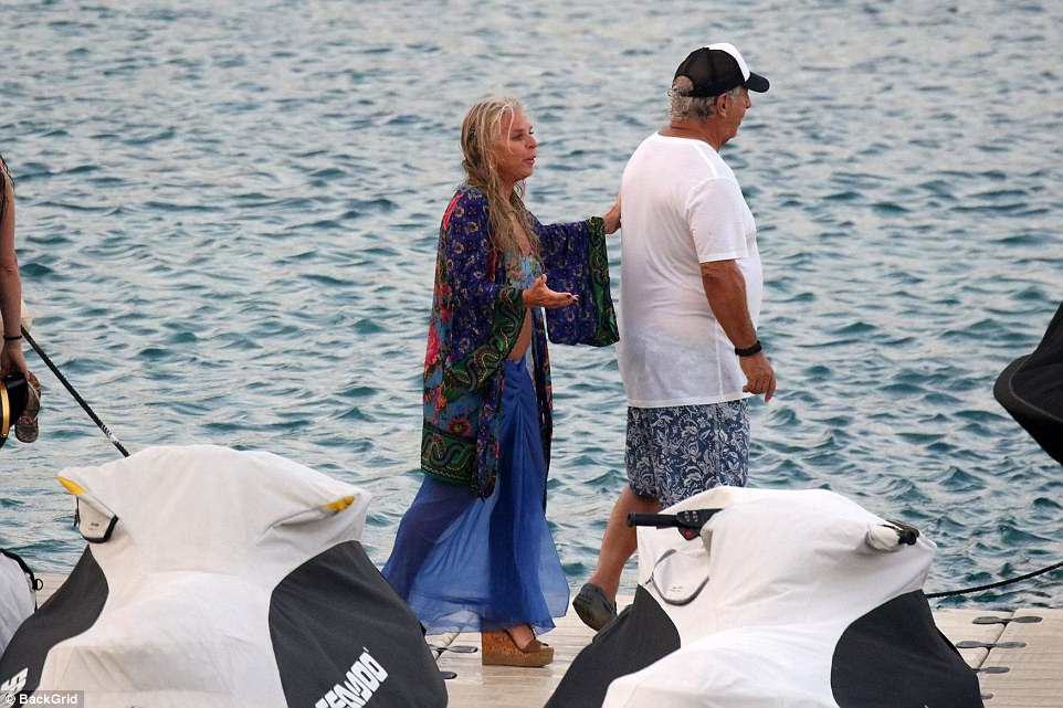 Sir Philip and his wife Tina were both dressed for the sun as they strolled along at the water's edge
