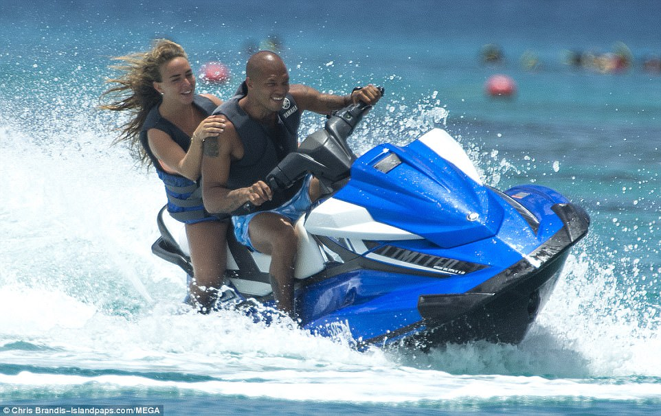 All-smiles: The pair couldn't contain their joy as they soaked up the sights of the island on their own jet ski