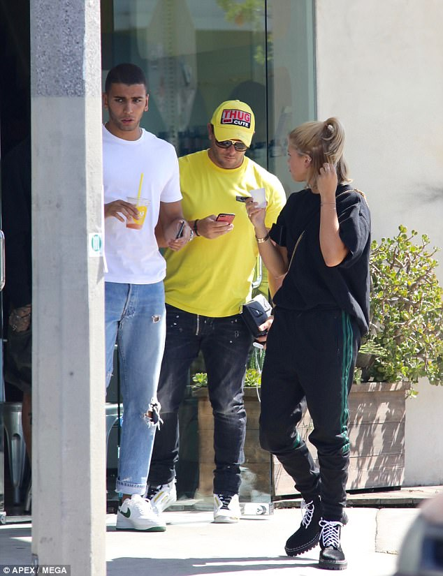 Boxer body: Younes covered his finely-toned physique in a plain white t-shirt and sported white and green Nike Air Force One's on his feet