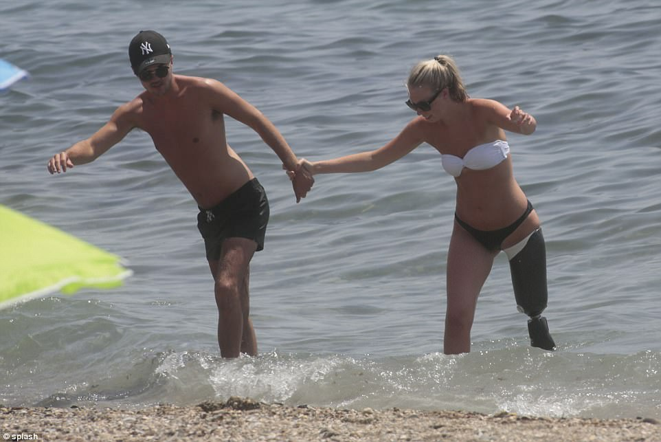 The couple held hands as they paddled in the sea on a sunny day in Marbella