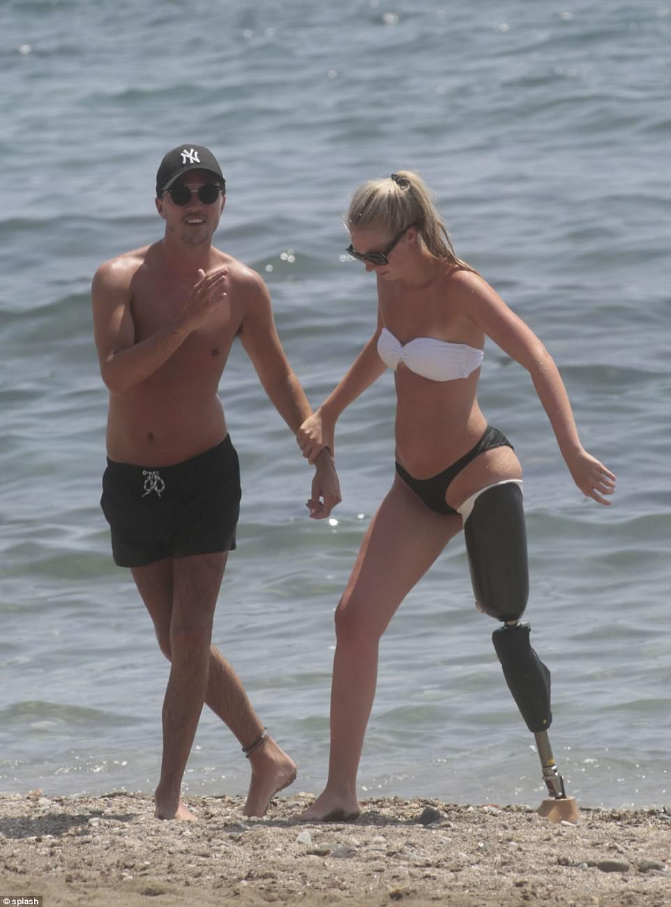 Joe lovingly helps his girlfriend off from the sea onto the beach during their Marbella trip