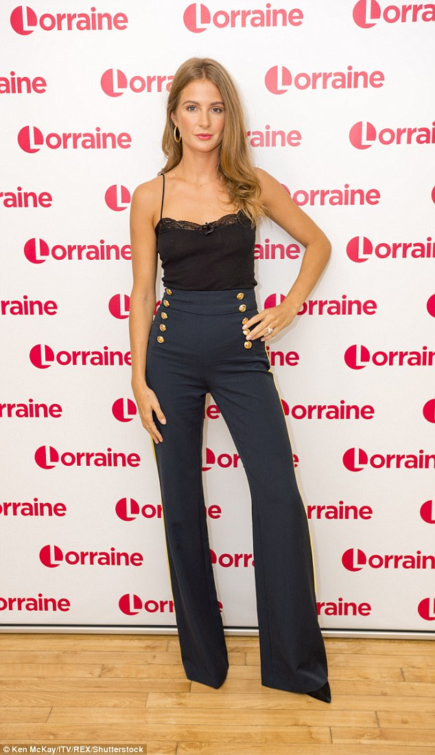 Stylish: Millie sported a simple, lace-trimmed vest top and smart trousers