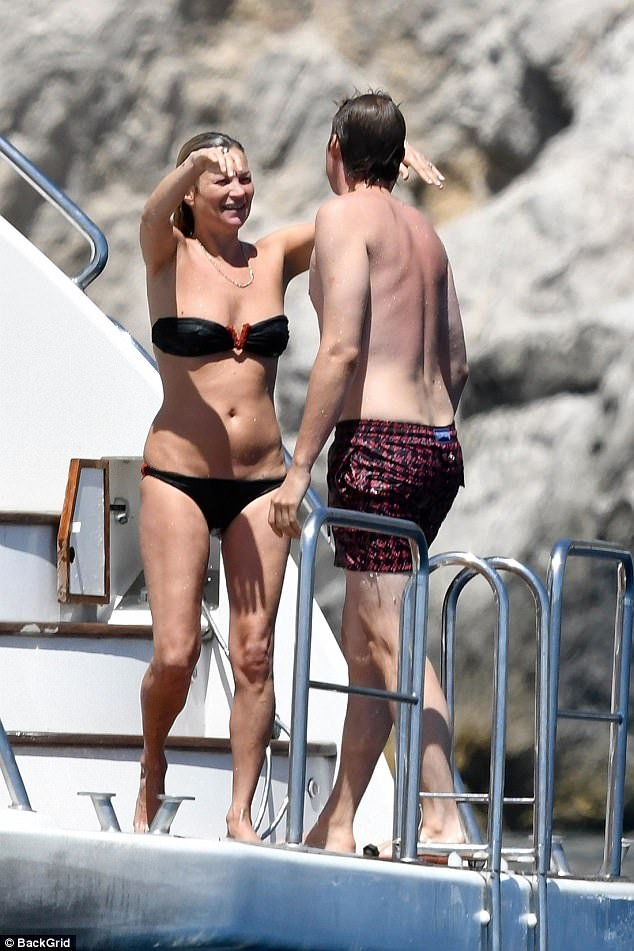 Locking lips: Nikolai, who donned maroon patterned swim shorts, also seemed infatuated with the British beauty as he approached her for a saucy kiss