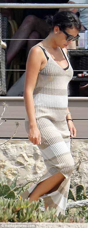 Beach chic: A peek of her bikini was visibly under the sartorially savvy number, which she paired with a pair of golden sandals