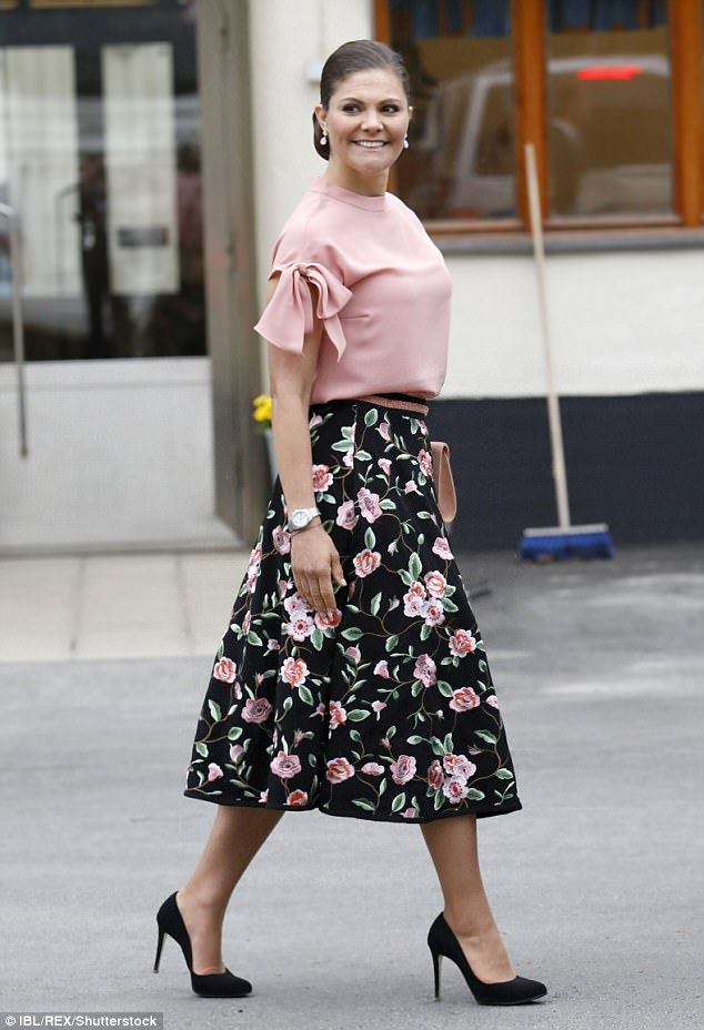 Crown Princess Victoria looked feminine in a floral print midi skirt and matching pink blouse as she arrived atStockholm Vatten water factory in Drottningholm
