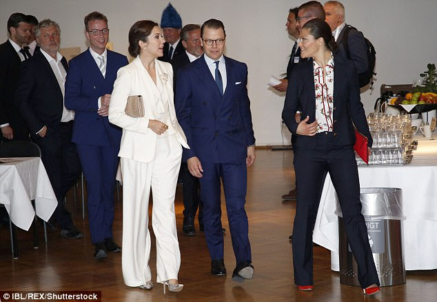 Mary opted for a cream loose fitting two piece while Victoria chose a traditional navy suit showcasing flashes of scarlet in the form of her accessories
